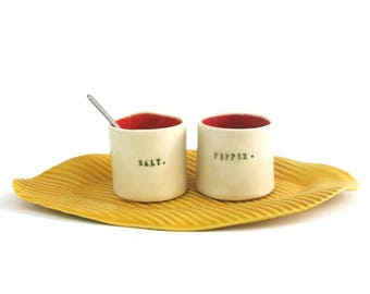 whimsical hand built porcelain salt and pepper cellars sitting on a tray   ...   red and yellow