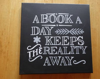 "Black canvas sign reads:""A book a day keeps the reality away"" white typography 12x12"" sign"