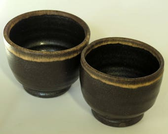 Small 'chawan' tea bowls inspired by Japanese Raku and Chinese Jian ware, black glaze with tan 'hare's fur' accents