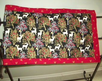 Christmas table runner with white reindeer, gold trees and red on black background.