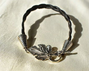 Silver braided horse hair with a leaf design toggle clasp.