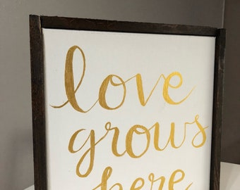 "Hand lettered canvas and wood sign ""Love grows here"""
