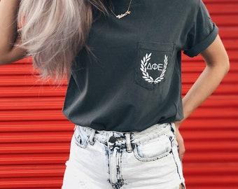 """Delta Phi Epsilon """"ΔΦΕ"""" Comfort Colors Laurel Unisex Pocket T-shirt"""