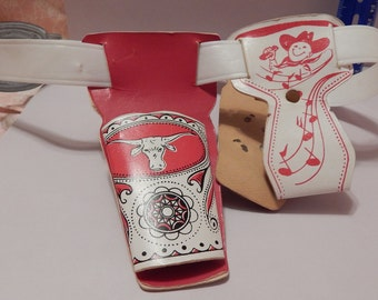 Small Red and White Toy Holster Set with ornate Metal Buckle , White Plastic Belt , Cowboy holding Harmonica with music notes