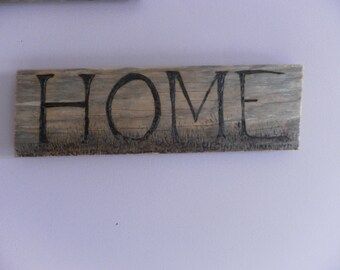 Home in a grassy field a sign for the home on old scrap wood pyrography for the wall of happy peaceful homes