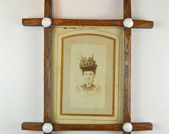 A Victorian photograph of a lady in elaborate hat oak frame with china jewells circa.1900