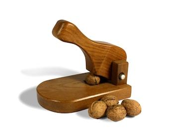 Crush walnuts and hazelnuts in walnut wood