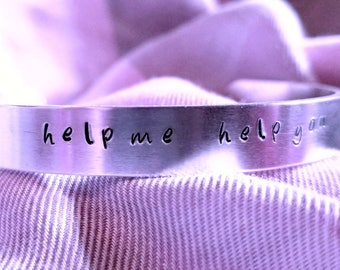 """Hand stamped cuff bracelet with """"help me help you""""."""