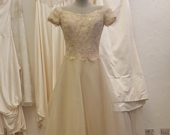 Vintage beige wedding dress with lace bodice and tulle skirt.