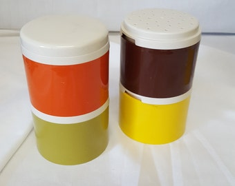 Tupperware spice towers with four jars in harvest colors of orange, olive green, brown and gold.