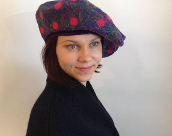 Original and stylish women's beret cool green and purple color with bright pink circles for the autumn-winter season.