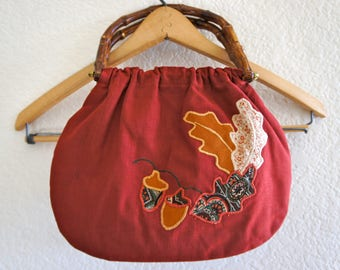 70s vintage handbag with bamboo handles and gold metal hardware and embroidered leaves design on front lined with cute cotton paisley fabric