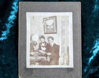 Beautiful haunting cabinet photo of a man and woman Victorian or Edwardian era mourning sitting at a table looking through albums