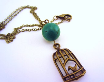Bird necklace, bird cage. Semiprecious deep turquoise blue stone, bronze chain. Love bird, deep sea blue. Charm necklace.