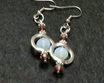 Moonstone dangle earrings floating in a silver oval accented with burgundy crystals