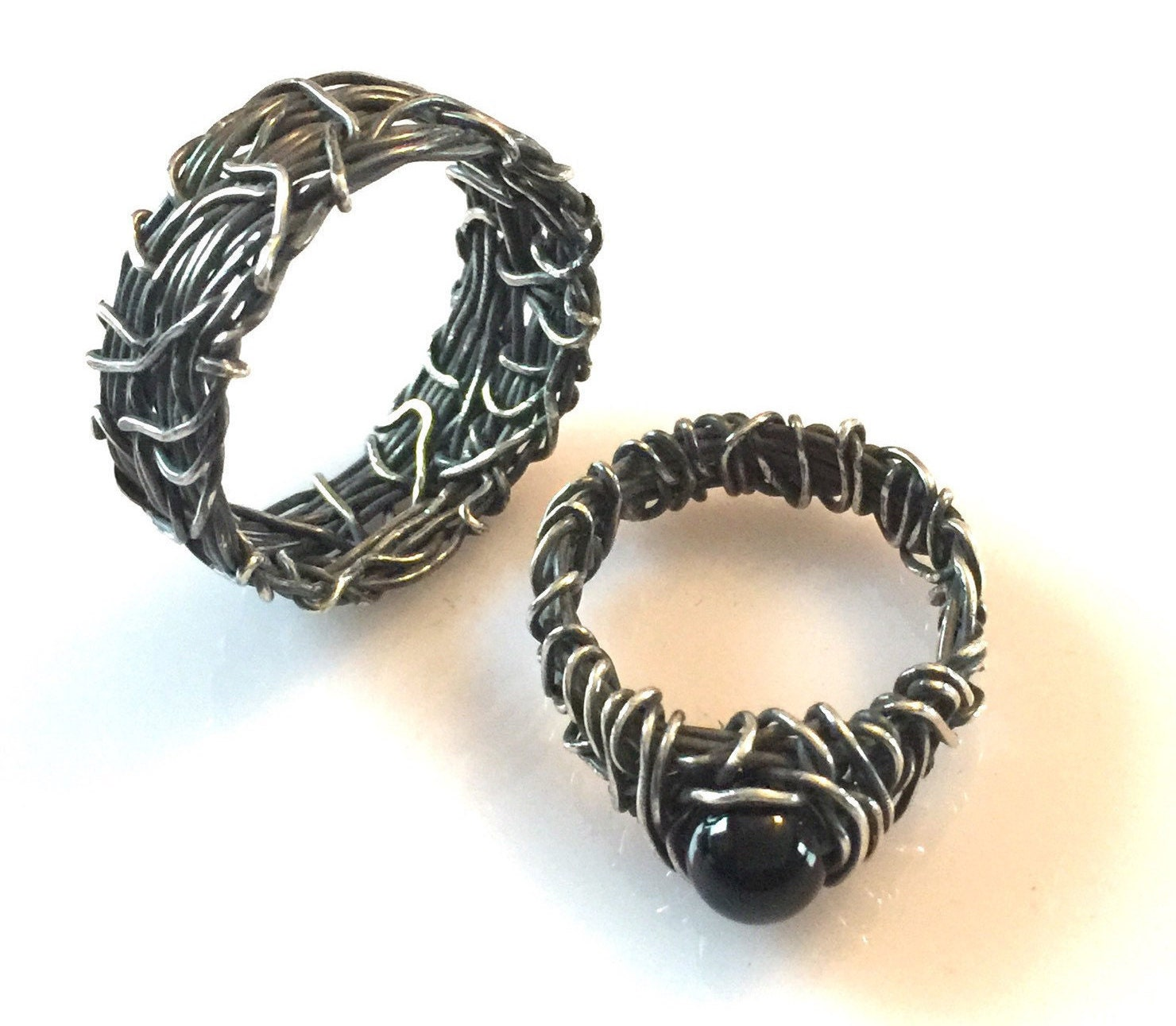 I would be honored to create this his and hers wedding ring set in oxidized sterling silver with an onyx stone. It is designed to reflect the matrimony of uniqu