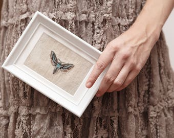 Embroidered moth in white frame
