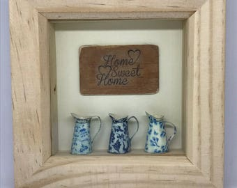 Three handmade miniature jugs displayed in a box frame with vintage style 'Home Sweet Home' plaque