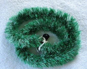 Green and white eyelash lei, finished with black kukui nuts, handmade in Hilo, Hawaii