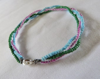 Three stand braided bracelet green, pale blue and pink/purple coloured