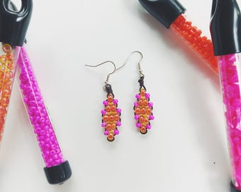 Hot pink and orange glass beaded earrings with brown leather cord.
