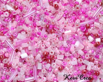 Set of 80g seed beads pink tones are various sizes and shapes