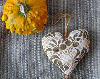 Decorative decoration in the form of a heart pattern with cross-stitch