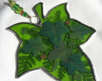 Lime green stained glass ivy leaf with ferns, ivy leaves and ladybirds.