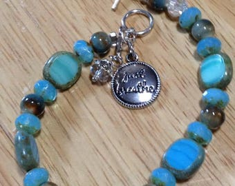 "Czech Glass Beads of various sizes and shapes with a Silver plated charm that says ""Just Breath"" and a crystal accent charm"
