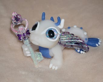 Polymer clay white fairy dragon with pink and purple glittery wings and wand