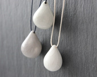 Handmade ceramic tear drop necklaces, gray or white, on dark blue or white cotton cord
