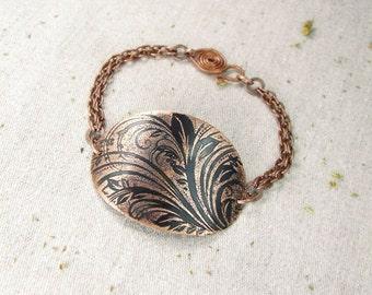 Copper bracelet with floral pattern.