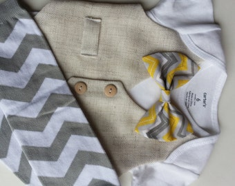 Baby Boy Bodysuit With An Ivory Vest Attached, A Chevron Grey, White, And Yellow Bow, And Chevron Grey And White Leg Warmers set.