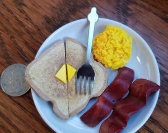 Scrambled eggs, 2 strips of bacon, buttered toast, on plate and with a fork inspired by American Girl and intended for doll play.