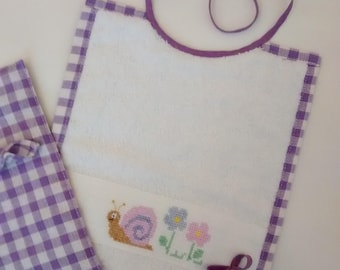 Table set comprising bib and washcloth embroidered in cross stitch.