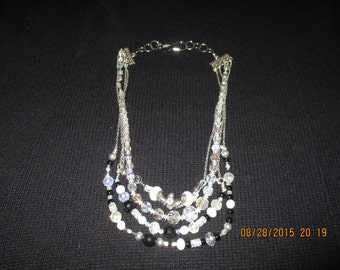 """Multi strand  22"""" necklace with black, white,crystal beads and embellishments with silvertone clasp"""
