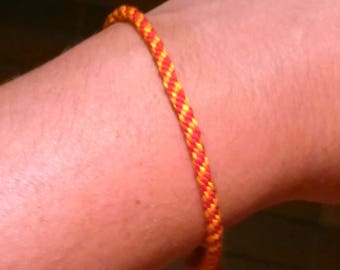 Kumihimo bracelet made of red, orange and yellow