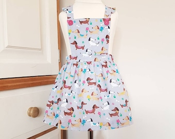 Sausage dog print cotton pinafore dress with ruffles available from age 1 to 6 years