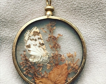 Handmade imitation pocket watch with herbarium and butterfly