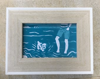 A Lino print of a dog & a boy paddling in the sea.