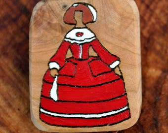 Juniper wood brooch with Menina dressed in red