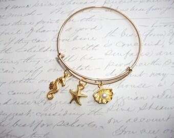 Seahorse starfish and and seashell charm gold bangle bracelet