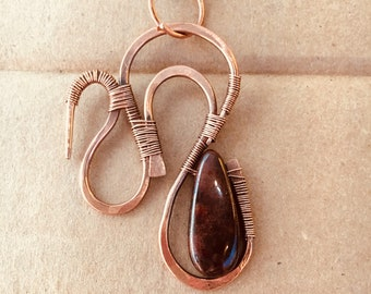 Copper wire  wrapped  pendant with garnet bead.