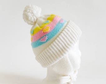 Vintage 1980s Baby Size 3M Knit Cap, White Acrylic Pastel Color Bands with Hearts Pom Pom Tassle Ear Flaps
