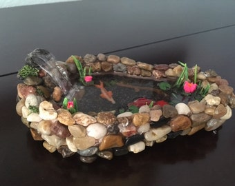Colorful miniature koi pond with water lilies, greenery, and waterfall