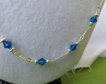 Blue crystal station necklace on silver chain with two pairs of matching earrings set