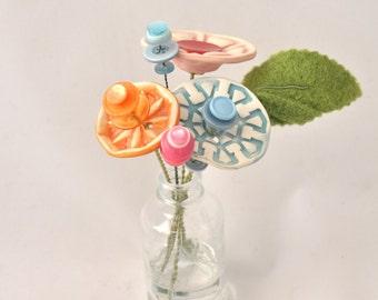 light blue, orange, and pink button flower bottle bouquet