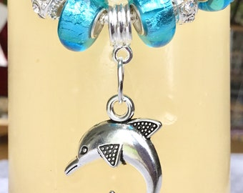 "A dolphin bangle with Aquamarine Murano beads matches the necklace. ""Aquamarine Dolphin Bangle ""."