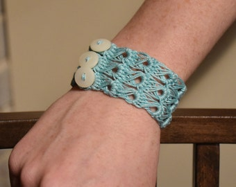 Light blue broomstick lace crocheted bracelet with buttons