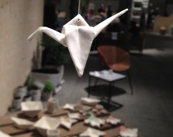 origami crane of porcelain: moij design's handmade decoration, a hanging ornament which has the appearance of folded paper